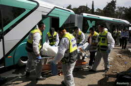 Members of Zaka Rescue and Recovery team carry a covered body from the scene of an attack on a Jerusalem bus, October 13, 2015.