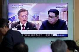 People watch a TV screen showing file footage of South Korean President Moon Jae-in and North Korean leader Kim Jong Un during a news program ahead of the inter-Korean summit at the Seoul Railway Station in Seoul, South Korea, April 26, 2018.