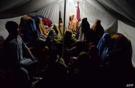 Women with their children sit inside a tent on the outskirts of Jalalabad, in Afghanistan's Nangarhar province, Jan 18, 2017.