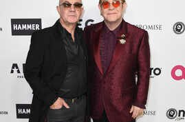 Elton John, right, and Bernie Taupin arrive at a celebration of Elton John's 70th birthday and 50-year songwriting partnership with Taupin on March 25, 2017 in Los Angeles.