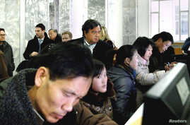 Former New Mexico Governor Bill Richardson (C, back row) looks at North Koreans working on computers at the Grand People's Study House in Pyongyang, January 9, 2013 in this picture released by the North Korea's KCNA news agency.