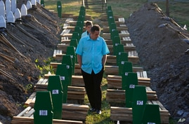 A Bosnian man walks among graves during a funeral ceremony for the 136 victims at the Potocari memorial complex near Srebrenica, 150 kilometers (94 miles) northeast of Sarajevo, Bosnia and Herzegovina, July 11, 2015.