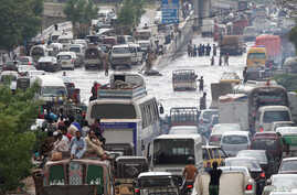 People and vehicles pass through a flooded road after the rain in Karachi, Pakistan, Aug. 31, 2017.