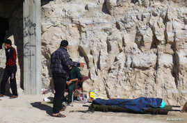 People stand near a dead body, after what rescue workers described as a suspected gas attack in the town of Khan Sheikhoun in rebel-held Idlib, Syria, April 4, 2017.