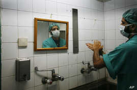 FILE - A Palestinian doctor washes his hands prior to performing a surgery at Shifa hospital in Gaza City, Jan. 27, 2009. Health officials see hand washing as the single most important measure for preventing surgical site infections.