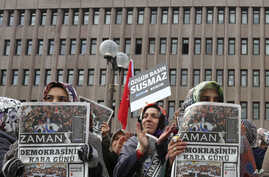 "Women hold copies of Zaman newspaper with a headline that reads ""the black day of democracy "" as they protest against the detention of its editor-in-chief a day ago in Istanbul, outside the Palace of Justice in Ankara, Turkey, Dec. 15, 2014."