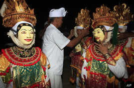 FILE - Balinese masked dancers prepare to perform during Hindu rituals of Odalan, a festival to observe a temple's anniversary, in Bali, Indonesia, Oct. 8, 2014.