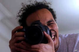 Mahmoud Abu Zaid, a photojournalist known as Shawkan, poses with his colleague's camera at his home in Cairo, Egypt, Monday, March 4, 2019. Shawkan was released after five years in prison.