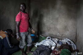 A health worker works to clean and dress the bodies of a young boy and man, who were killed the night before, allegedly by rebels from the Allied Democratic Forces, Oct. 5, 2018 in Beni, in the Democratic Republic of the Congo.
