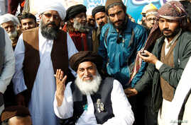 Khadim Hussain Rizvi, center, leader of Tehreek-e-Labbaik Pakistan islamist political party, gestures at their protest site at Faizabad junction in Islamabad, Pakistan, Nov. 27, 2017.