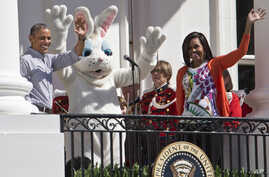 President Barack Obama and first lady Michelle Obama wave with the Easter Bunny as they greet families participating in the White House Easter Egg Roll on the South Lawn of White House in Washington, April 6, 2015.