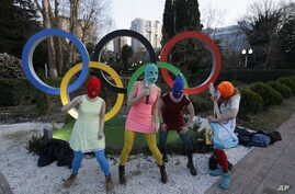 Members of the punk group Pussy Riot, including Nadezhda Tolokonnikova in the aqua balaclava, center, and Maria Alekhina in the red balaclava, left, perform next to the Olympic rings in Sochi, Russia, on Wednesday, Feb. 19, 2014.