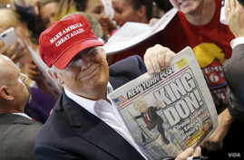 """Republican presidential candidate Donald Trump holds up the front page of the New York Post as he signs autographs in Harrington, Delaware, April 22, 2016. The Post called him """"King Don"""" after his New York primary victory, but it had predicted his ca"""