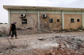 A member of the February 17th Brigade walks the base after it was bombed by two jets, Benghazi, May 28, 2014.