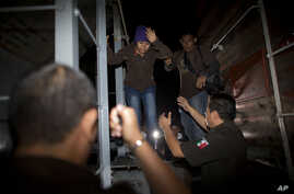 Immigration officials remove Central American migrants from a northbound freight train during a raid by federal police in San Ramon, Mexico, Aug. 29, 2014.