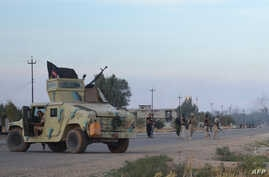 Iraqi pro-government forces stand guard on a road during a major operation against Islamic State fighters to retake the town and areas around Saadiya, northeast of Baghdad in Diyala province, Nov.  23, 2014.