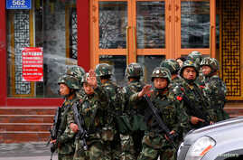 Paramilitary policemen gesture to stop a photographer from taking pictures as they stand guard after an explosives attack hit downtown Urumqi in the Xinjiang Uighur Autonomous Region May 23, 2014.