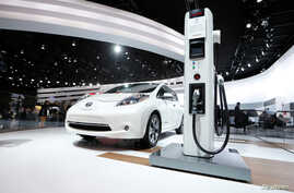 FILE: A Nissan Leaf electric car is displayed next to a charging stand at the North American International Auto Show in Detroit, Jan.12, 2016. The Leaf is one of many Nissans that will come with automatic braking standard in the 2018 model year.