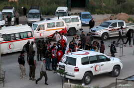 Buses and ambulances evacuating people from four besieged Syrian towns wait at an exchange point supervised by the Syrian Arab Red Crescent, in the town of Qalaat al-Madiq, in Hama province, Syria, April 21, 2016.