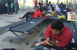 """Many refugees sleep outside Austria station, refusing government provided housing after word """"camp"""" became associated with detentions in recent months, Sept. 15, 2015. (Photo: H. Murdock / VOA)"""
