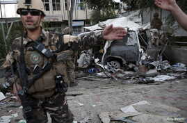 Members of Afghan security forces keep watch in front of a damaged car that belongs to foreigners after a bomb blast in Kabul, Afghanistan, Aug. 22, 2015.