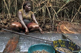 A woman coated in oil perches near a mangrove after fishing in a creek near the River Nun in Nigeria's oil state of Bayelsa, November 27, 2012.,