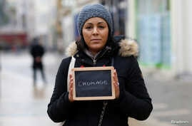 """FILE - Malika Etchekopar-Etchart, unemployed, holds a blackboard with the word """"chomage"""" (unemployment), the most important election issue for her, as she poses for Reuters in Chartres, France."""