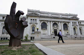 FILE - A man walks past the historic Carnegie Library building in Washington. Philanthropist Andrew Carnegie funded 3,000 public libraries in English-speaking countries. Like Carnegie, philanthropists today are pouring money into a global drive to ma