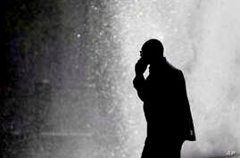 In this Oct. 11, 2012 file photo, a pedestrian talking on a cellphone is silhouetted in front of a fountain in Philadelphia.