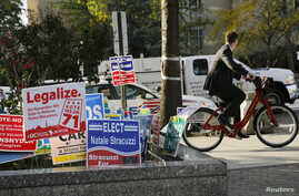 A cyclist peddles past a DC Cannabis Campaign sign, second from left, in Washington, D.C., Nov. 4, 2014.