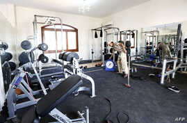 A member of the Fajr Libya (Libya Dawn) Islamist militia stands at the gym of a villa at the U.S. diplomatic compound after members of the group moved into the complex of several villas in southern Tripoli to prevent it from being looted, Aug. 31, 20