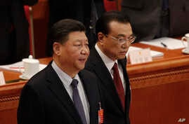 Chinese President Xi Jinping, left, and Chinese Premier Li Keqiang arrive at the opening session of China's National People's Congress at the Great Hall of the People in Beijing, Tuesday, March 5, 2019.