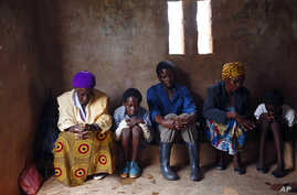 FILE - HIV-positive members of a self-help group pray at the start of a meeting in the village of Michelo, southern Zambia, Feb. 23, 2015.