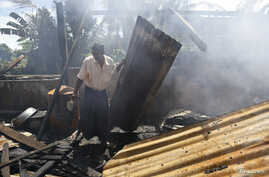 A man clears debris from the mosque that was burnt down in recent violence at Thapyuchai village, outside of Thandwe, in the Rakhine state, October 3, 2013. Security forces raced to contain deadly violence in Myanmar's Rakhine state on Tuesday, polic