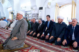Syria's President Bashar al-Assad (3rd R) attends prayers on the first day of the Muslim holiday of Eid al-Fitr, inside a mosque in Hama, in this handout picture provided by SANA, June 25, 2017, Syria.