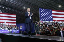 President Donald Trump walks toward the podium to speak at a rally at Total Sports Park, April 28, 2018, in Washington, Mich.