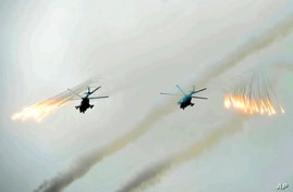 FILE - Russian Army helicopters fire flares over Sakhalin Island during military exercises, July 16, 2013.