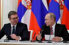 Russian President Vladimir Putin, right, and Serbian President Aleksandar Vucic talk to each other during a meeting with the media following their talks in the Kremlin in Moscow, Russia,  Dec. 19, 2017.