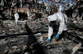 Forensics experts gather evidence in the rubble of a funeral hall destroyed by a deadly Saudi-led airstrike on Oct. 8, 2016, in Sanaa, Yemen.