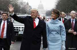 President Donald Trump waves as he walks with first lady Melania Trump and son Barron during the inauguration parade on Pennsylvania Avenue in Washington, Jan. 20, 2017.