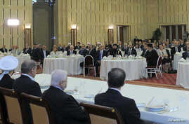 Syria's President Bashar al-Assad (L) delivers a speech while attending an Iftar, or breaking fast session, during the Muslim month of Ramadan in Damascus, Aug. 4, 2013.