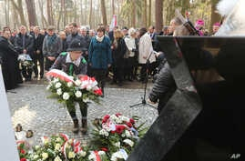 A girl scout lays a wreath at the central monument of a cemetery near the village of Jagiella, in southern Poland, Thursday, March 17, 2016 during ceremonies remembering the Ulma family and eight Jews they were sheltering during Holocaust, all of who