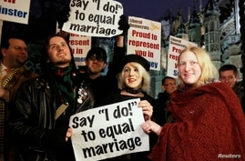 """Campaigners demonstrate for a """"yes"""" vote to allow gay marriage, as they protest outside Parliament in London, February 5, 2013."""
