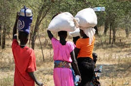 In this photo taken Dec. 7, 2018, women and girls walk back after getting food in Bentiu, a 38 kilometers (24 miles) journey using a path through the bush for fear of being attacked on the main road, near Nhialdu in South Sudan