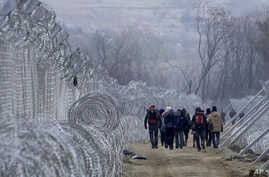 Refugees and migrants, who entered Macedonia from Greece illegally, walk between the two lines of the protective fence along the border line, near southern Macedonia's town of Gevgelija, Monday, Feb. 29, 2016.