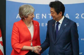 Britain's Prime Minister Theresa May, left, and Japan's Prime Minister Shinzo Abe shake hands prior to a bilateral meeting at the G20 Leader's Summit in Buenos Aires, Dec. 1, 2018.