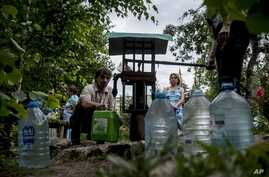Local citizens line up to collect water, in a street in the center of Slovyansk, eastern Ukraine, July 13, 2014.