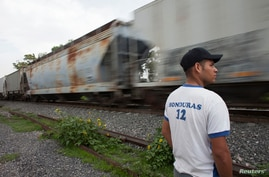 FILE - A migrant from Honduras stands by a passing train in Atitalaquia, on the outskirts of Mexico City June 26, 2014.