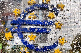 The Euro sculpture in front of the old European Central Bank building is photographed behind rain drops on a window in Frankfurt, Germany, Oct. 18, 2016.