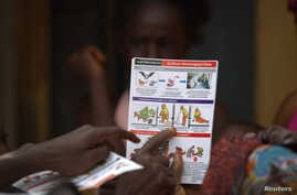 A UNICEF worker shares information on Ebola and best practices to help prevent its spread with residents of the Matam neighborhood of Conakry, Guinea in this handout photo courtesy of UNICEF taken Aug. 20, 2014.